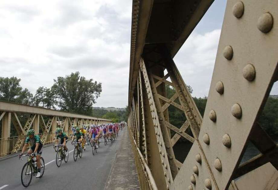 The pack with Thomas Voeckler of France, wearing the overall leader's yellow jersey, crosses a bridge during the 10th stage of the Tour de France. Photo: Christophe Ena, Associated Press