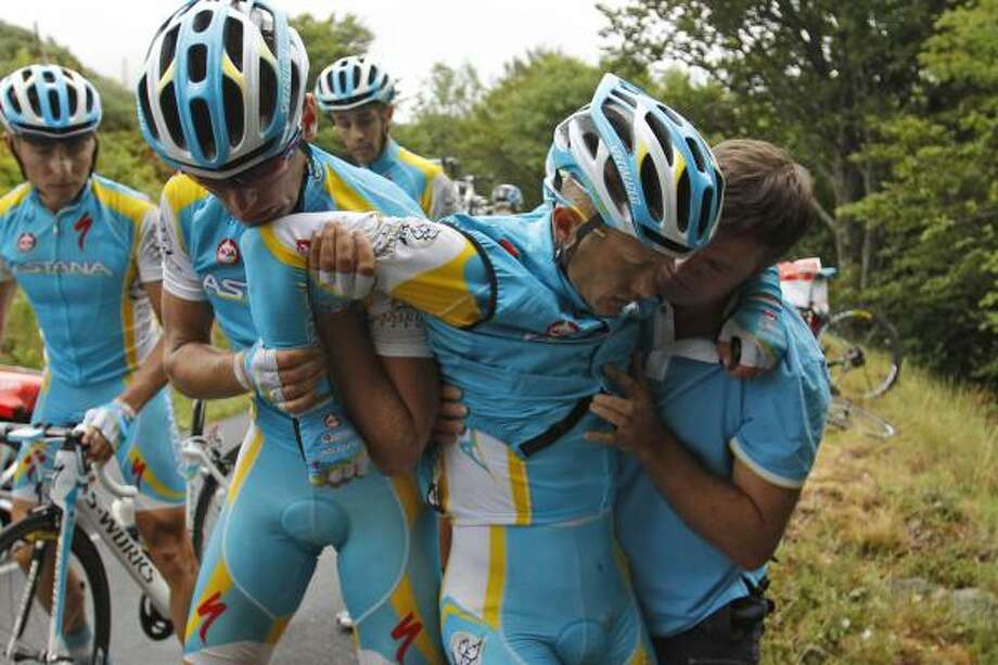 Alexande Vinokourov of Kazakhstan, second right, is helped by his teammates after crashing during the ninth stage. Photo: Christophe Ena, Associated Press