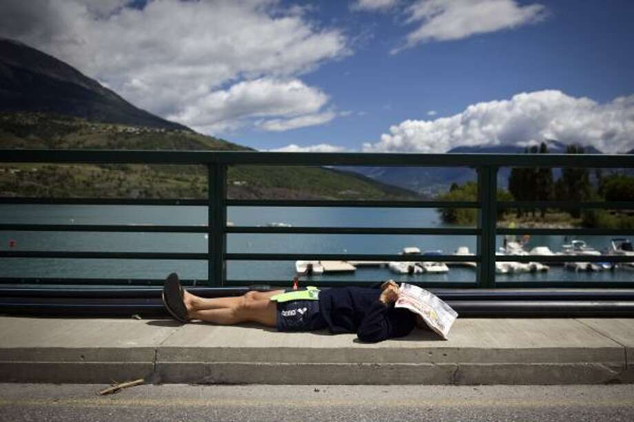 A fan, his face protected from the sun with a newspaper, rests on Sarrazin bridge during the 179 km and 17th stage. Photo: LIONEL BONAVENTURE, Getty