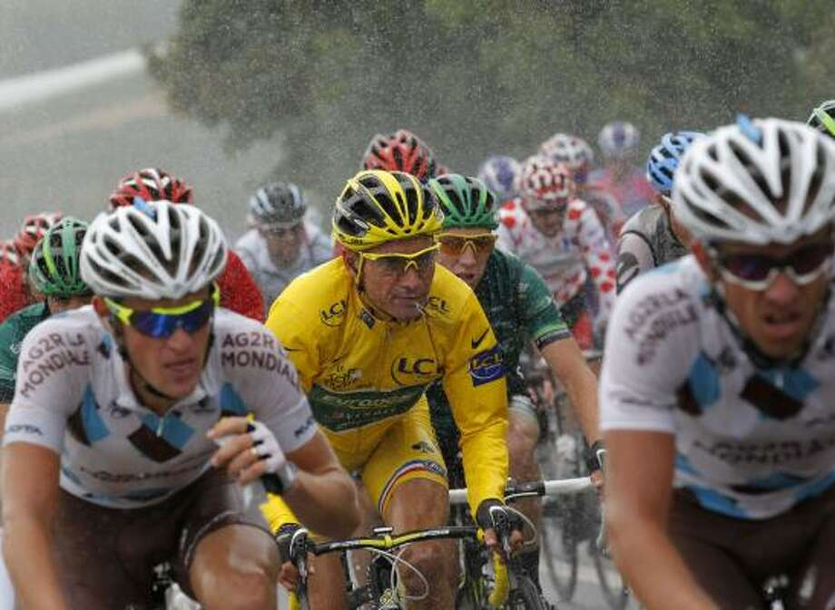 The pack with Thomas Voeckler of France, wearing the overall leader's yellow jersey, rides in the rain during the 16th stage of the Tour de France. Photo: Christophe Ena, Associated Press