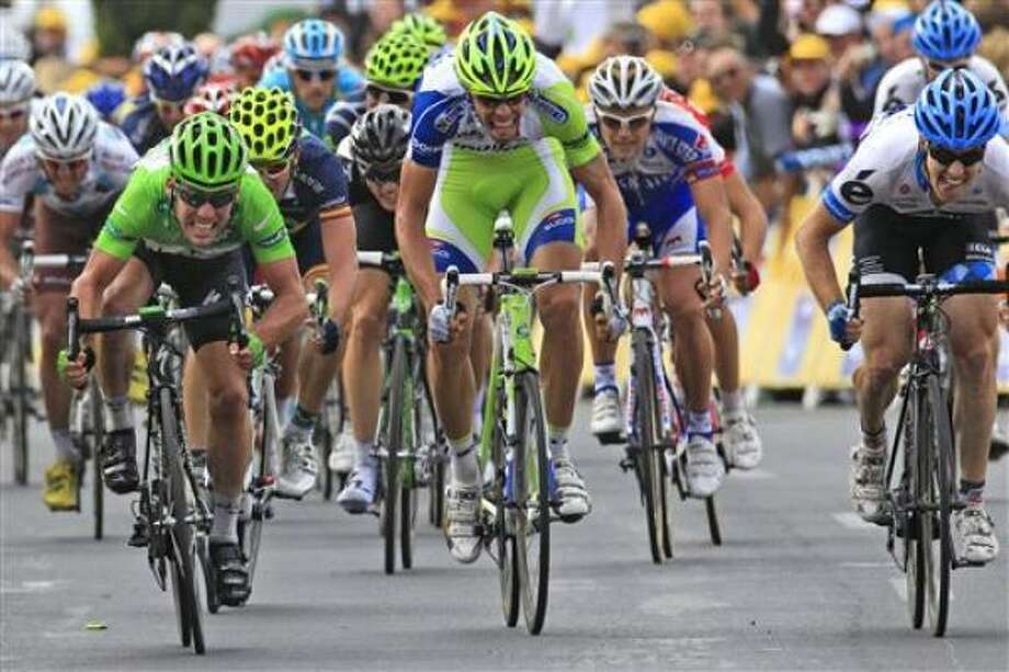 Mark Cavendish of Britain, wearing the best sprinter's green jersey, crosses the finish line ahead of Daniel Oss of Italy, right, to win the 15th stage of the Tour de France. Photo: Laurent Rebours, AP
