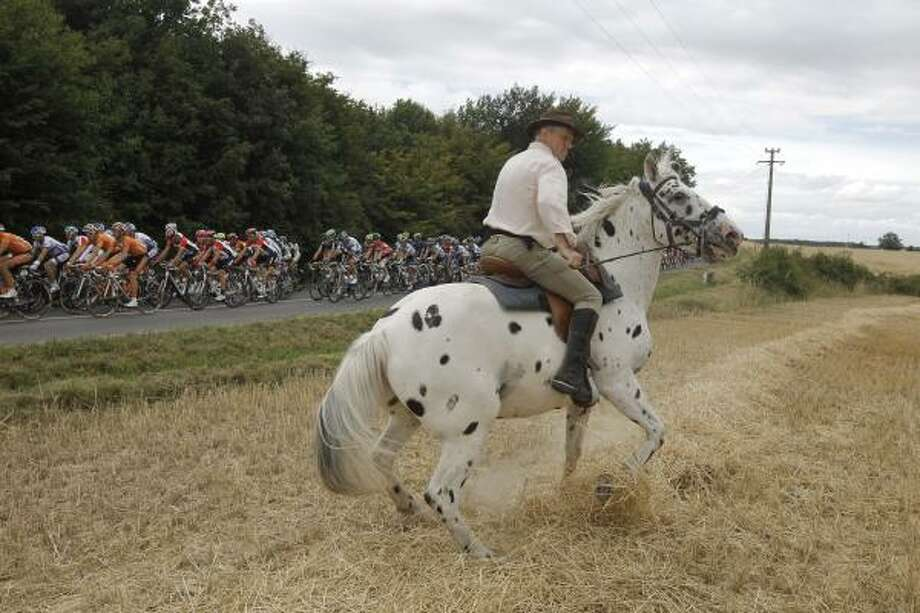 A man controls his horse as the pack passes during the seventh stage. Photo: Laurent Cipriani, Associated Press