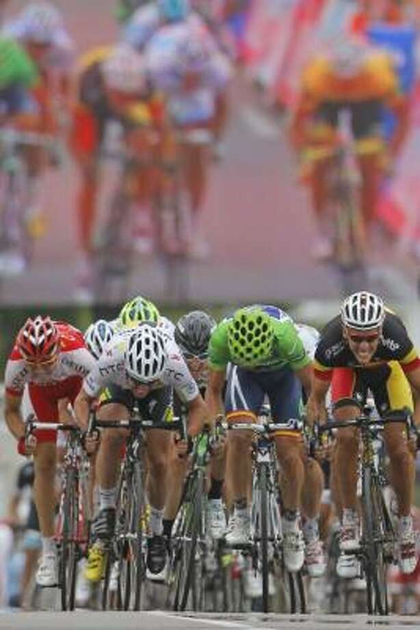 The last meters of the sprint are projected on a video wall, top, as Mark Cavendish of Britain, second left, strains in the last meters to win ahead of Philippe Gilbert of Belgium, right and second place, Jose Joaquin Rojas of Spain, center in best sprinter's green jersey and third place, and Tony Gallopin of France, far left and fourth place, during the fifth stage. Photo: Christophe Ena, Associated Press
