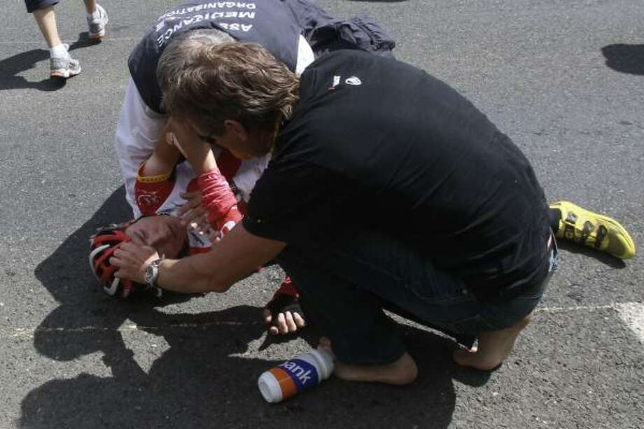 A Tour de France medic and a team member tend to Janez Brajkovic of Slovenia who crashed and subsequently abondoned the race. Photo: Christophe Ena, Associated Press
