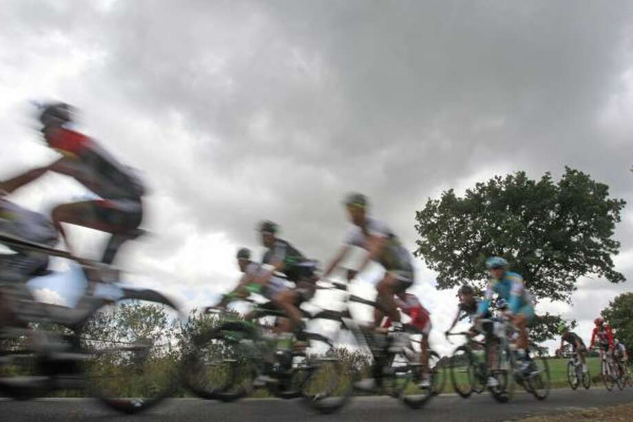 Riders are blurred by the use of a slow shutter speed on the camera as the pack passes. Photo: Christophe Ena, Associated Press