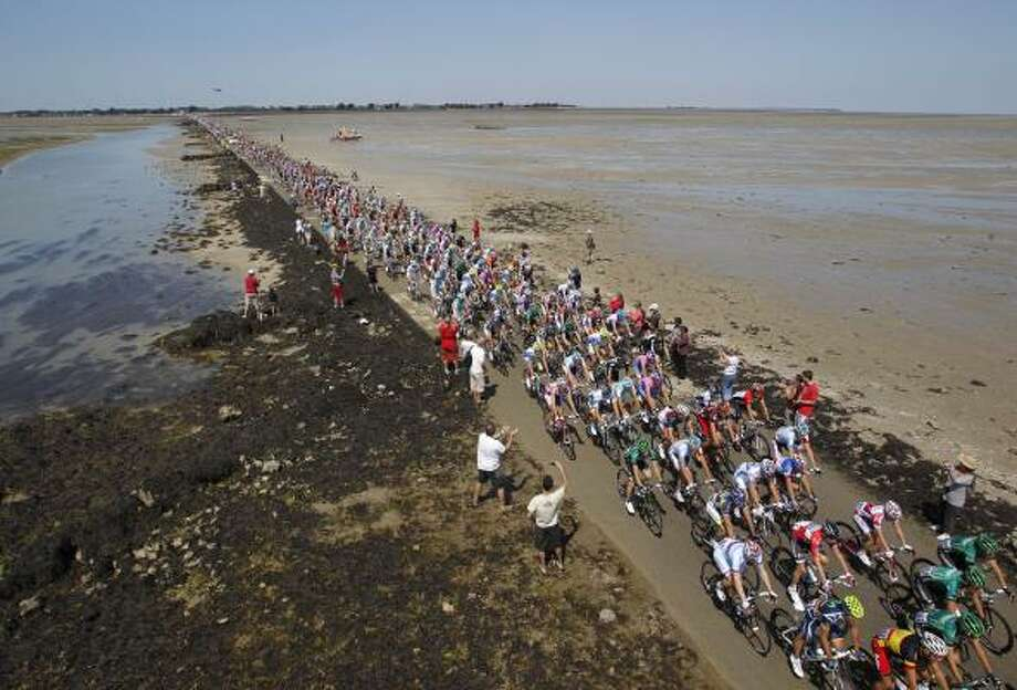 The pack passes the Passage du Gois, a causeway submerged by the tide twice a day joining Noirmoutier island, rear, and the mainland, during the first stage of the Tour de France. Photo: Christophe Ena, Associated Press
