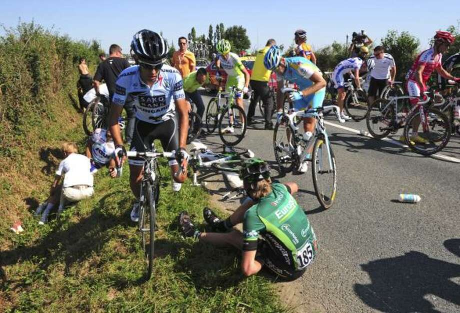 Riders get back on their bicycles after a crash in the last 10 kilometers of the first stage of the Tour de France. Photo: Stephane Mantay, Associated Press
