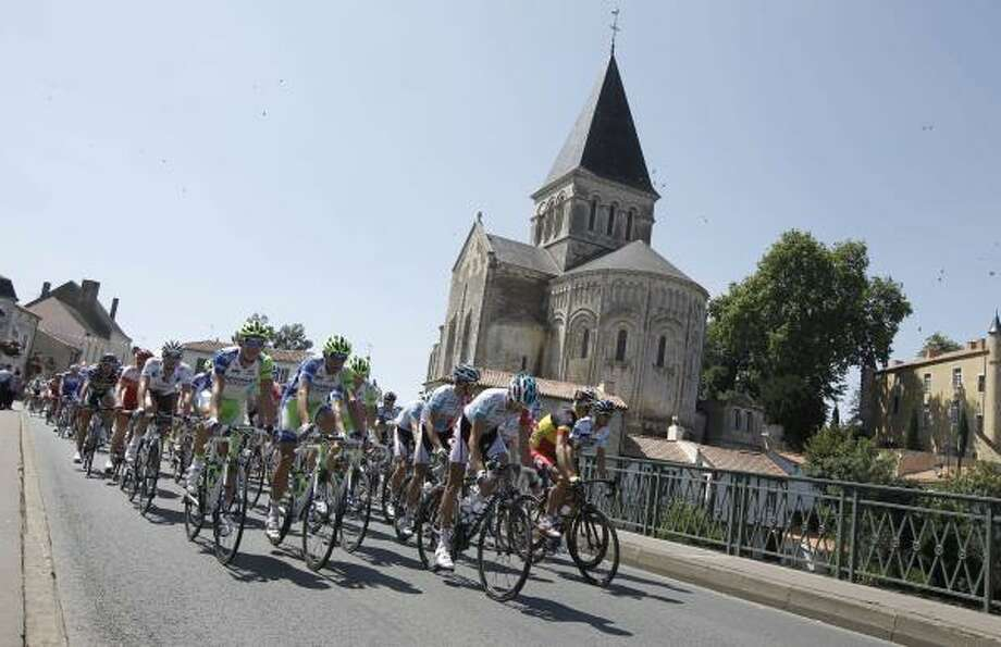 The peloton passes a church during the first stage of the Tour de France. Photo: Laurent Cipriani, Associated Press