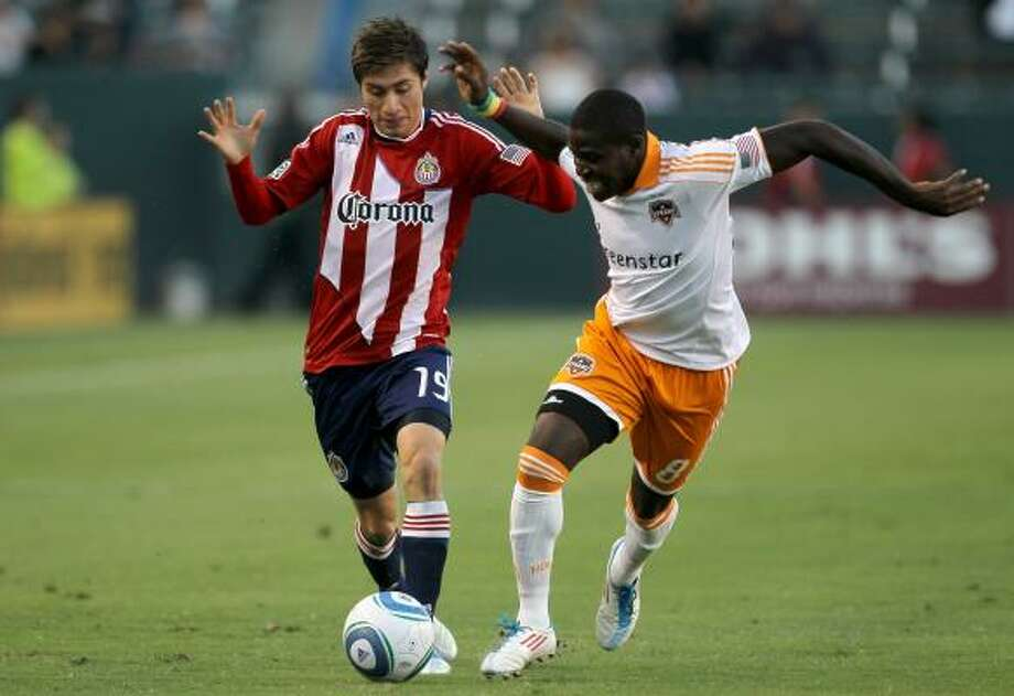 Dynamo defender Kofi Sarkodie, right, fights for the ball with Chivas USA's Jorge Flores during Saturday night's match at The Home Depot Center in Carson, Calif. Photo: Stephen Dunn, Getty