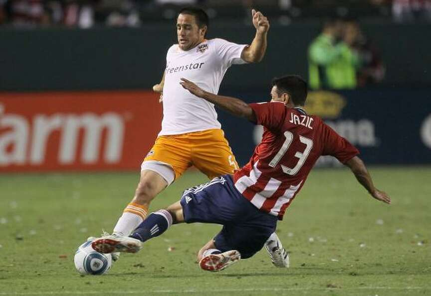 Dynamo midfielder Danny Cruz, left, tries to control the ball against Chivas USA's Ante Jazic.