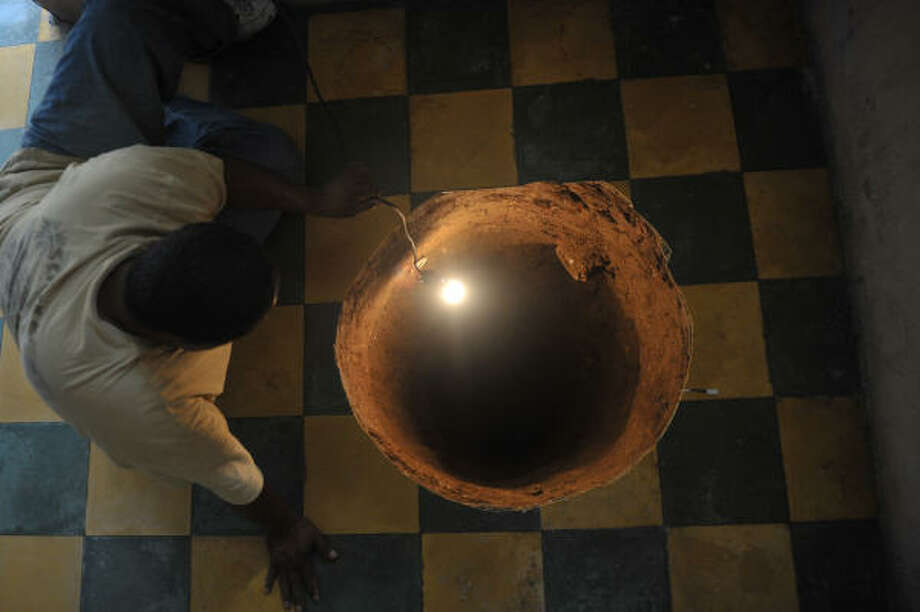 A man inspects a sinkhole formed in a house on July 19, 2011, in the north of Guatemala City, Guatemala. When neighbors heard the loud boom overnight they thought a cooking gas canister had detonated. Instead they found a deep sinkhole the size of a large pot inside a home. The sinkhole was 12.2 meters (40 feet) deep and 80 centimeters (32 inches) in diameter. Photo: JOHAN ORDONEZ, Getty
