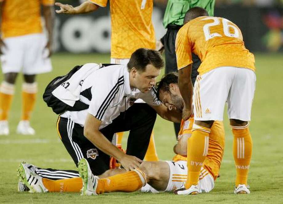 Defender Eddie Robinson of the Houston Dynamo is looked at by team trainer Theron Enns as teammate Corey Ashe looks on after he was injured. Photo: Bob Levey, Getty