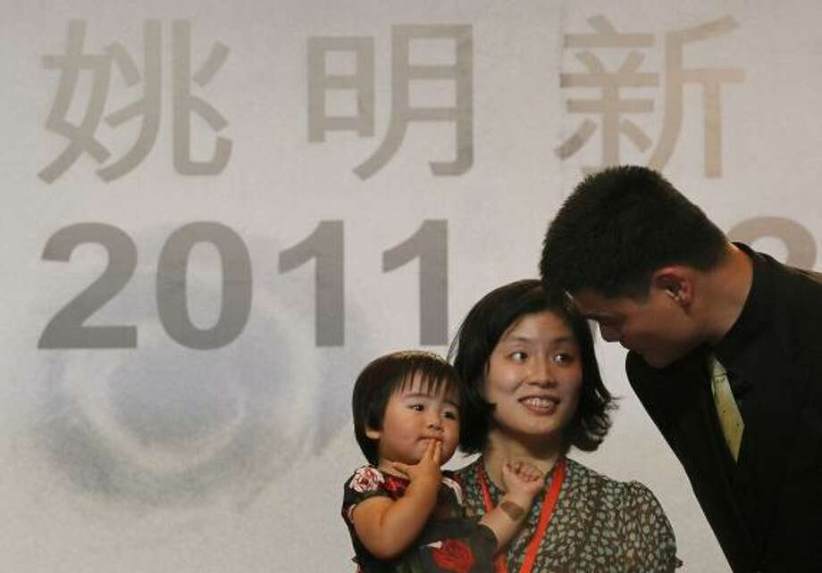 Former Rockets star star Yao Ming speaks to his wife Ye Li Yao and his daughter Qinle during a press conference in Shanghai, China, Wednesday, in which he announced his retirement. Photo: Eugene Hoshiko, Associated Press