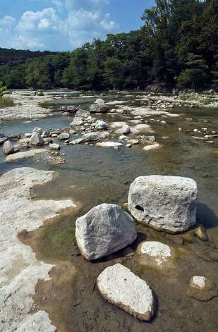 Rocks, which are normally covered with rushing water, now stand high and dry in the drought-stricken Guadalupe River. Photo: TOM REEL, SAN ANTONIO EXPRESS-NEWS / SAN ANTONIO EXPRESS-NEWS