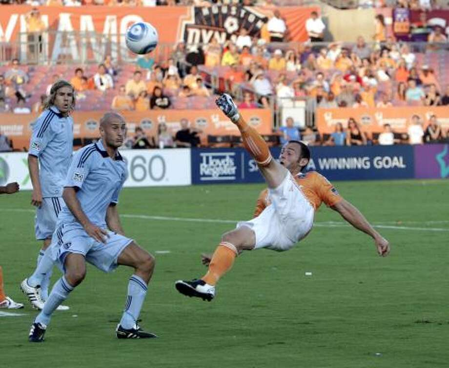 July 16: Dynamo 1, Kansas City 1Dynamo midfielder Brad Davis, right, puts a shot back on goal in front of Kansas City's Aurelien Collin, center, and Chance Myers. Davis scored in the eighth inning to give the Dynamo an early 1-0 lead. Photo: Bob Levey, Getty Images