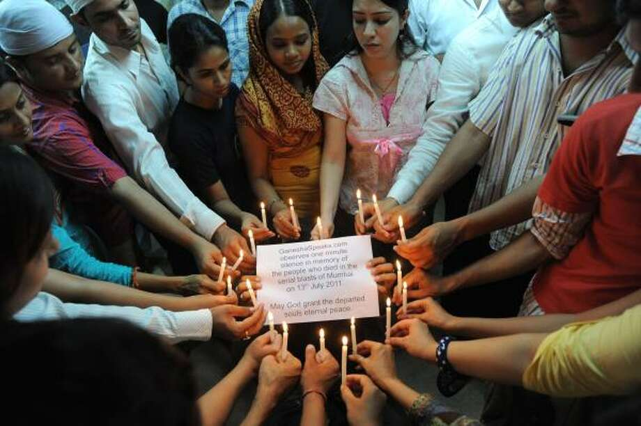 Indians participate in a candle-light vigil in memory of those who died and were injured in a series of three bomb blasts that hit Mumbai Wednesday. Photo: SAM PANTHAKY, Getty