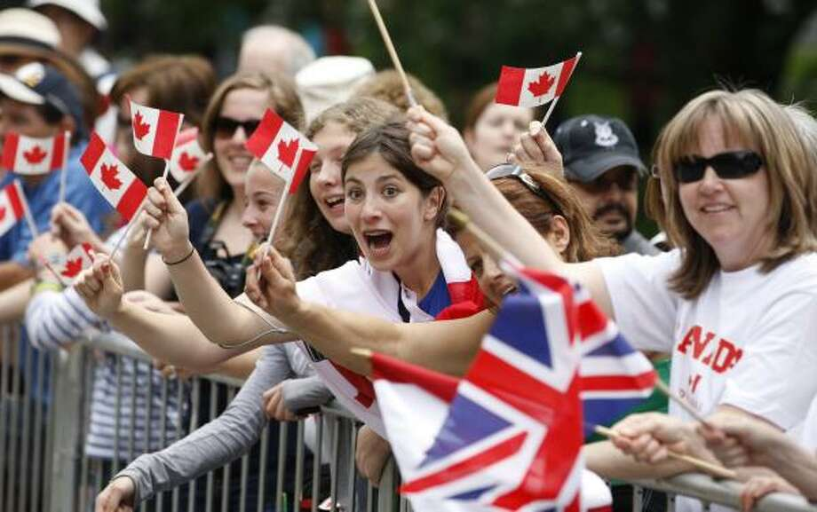 Crowds wave flags outside Rideau Hall in Ottawa. Photo: Adrian Wyld, Associated Press