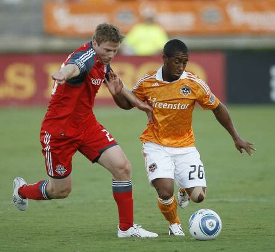 Dynamo 2, Toronto FC 0 Corey Ashe #26 of the Houston Dynamo fends off Jacob Peterson #23 in the first half. Photo: Bob Levey, Getty
