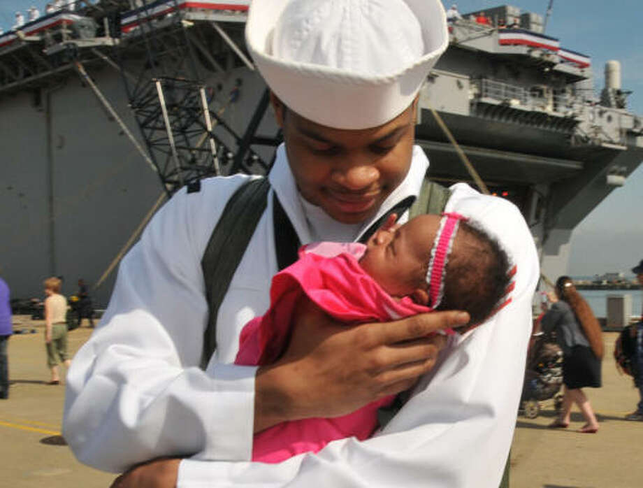 Who: Machinist's Mate Fireman Demontay Blue. Where:  Norfolk, Va. When: May 16, 2011.  Details: The sailor from the USS Kearsarge is holding his daughter for the first time. Photo: MC2 Rafael Martie, Associated Press