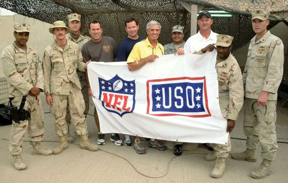 U.S. troops serving in Kuwait pose with (center, from left) Texans head coach Gary Kubiak, former head coach turned NFL Network analyst Jim L. Mora, former Saints and Colts head coach Jim E. Mora, and Cardinals head coach Ken Whisenhunt on Friday. This is the first USO tour for the group, which joins the list of NFL coaches to travel overseas on USO entertainment tours. Photo: Steve Manuel, USO Photo