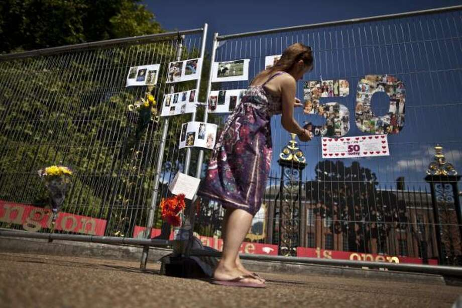 Princess Diana fan Kathy Martin, who has lived in London for about 15 years and is originally from Australia, makes adjustments as she puts up a homemade Diana 50th birthday tribute upon a fence outside Kensington Palace in London. Photo: Matt Dunham, Associated Press