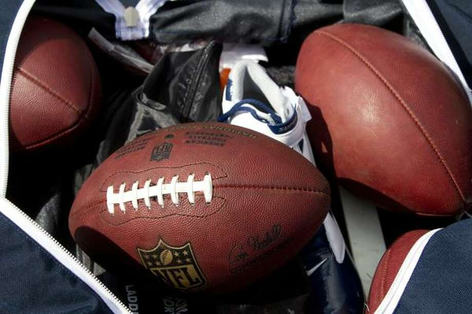 Footballs sit in a bag on the field during a players' minicamp at Rice Stadium. Photo: Brett Coomer, Chronicle