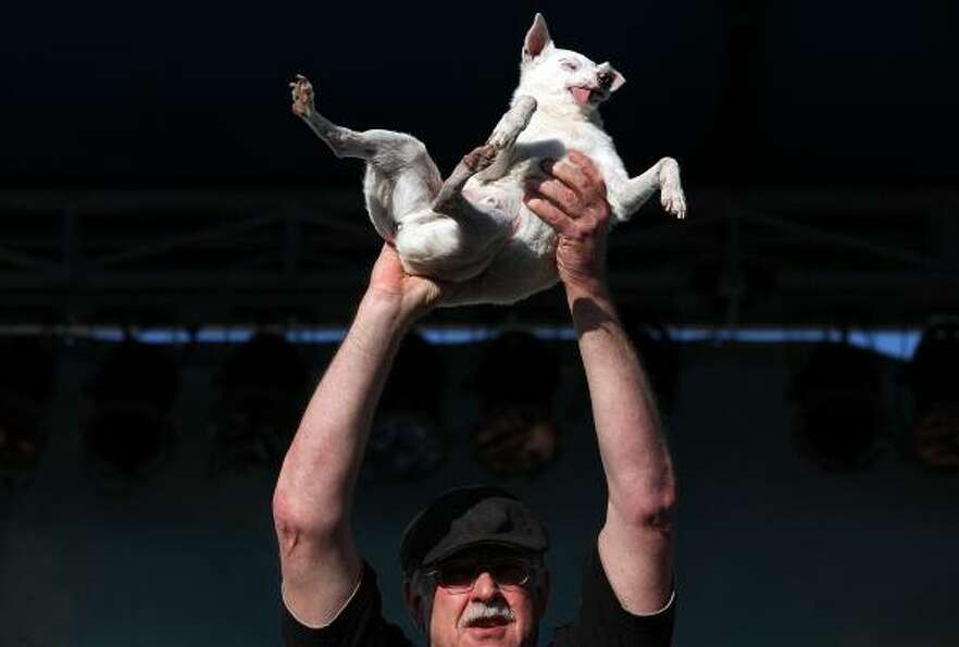 A contestant holds up his ugly dog.