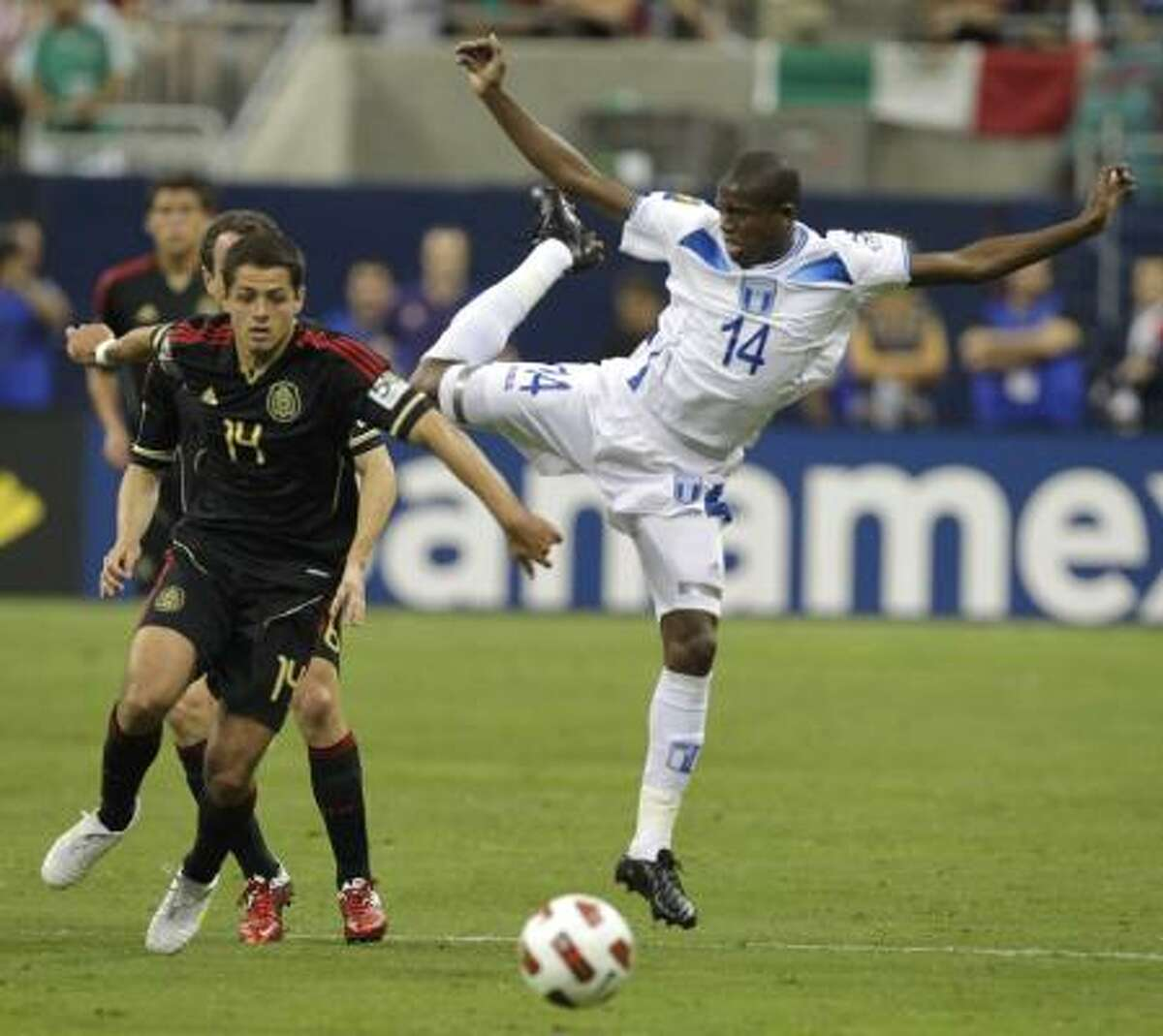 Honduras' Oscar Boniek Garcia, right, loses his balance while losing possession of the ball in the first half.