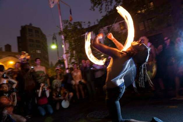 Tim Doody, of the West Village, fire spins for the crowds. Photo: John Minchillo, Associated Press