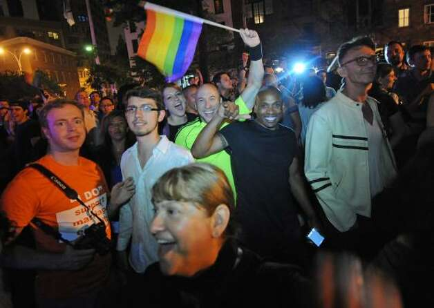 Revelers celebrate in Manhattan's west village following the passing of the same sex marriage bill. Photo: Louis Lanzano, Associated Press
