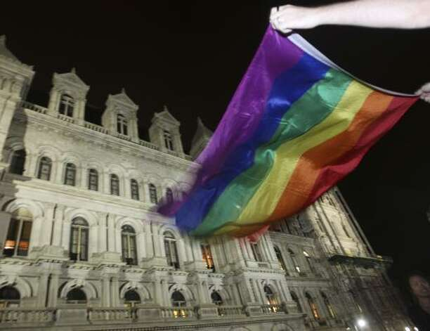 Robert Moore of New York waves a Pride flag outside the Capitol in Albany, N.Y., after the state Senate passed a bill legalizing same-sex marriage. Photo: Mike Groll, Associated Press