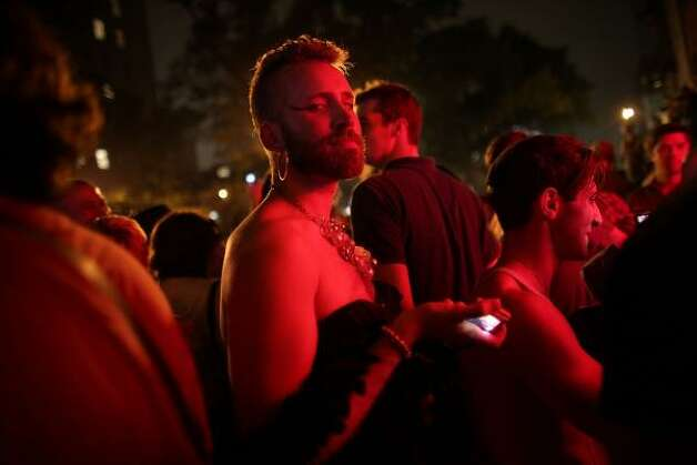 A reveler looks on as people celebrate in front of the historic gay bar The Stonewall. Photo: Spencer Platt, Getty
