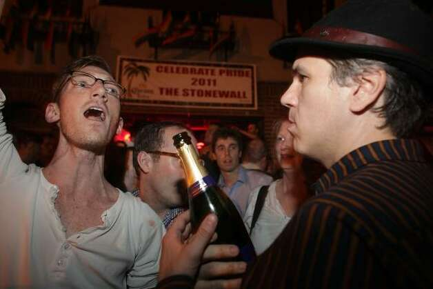 Revelers celebrate in front of the historic gay bar The Stonewall. Photo: Spencer Platt, Getty