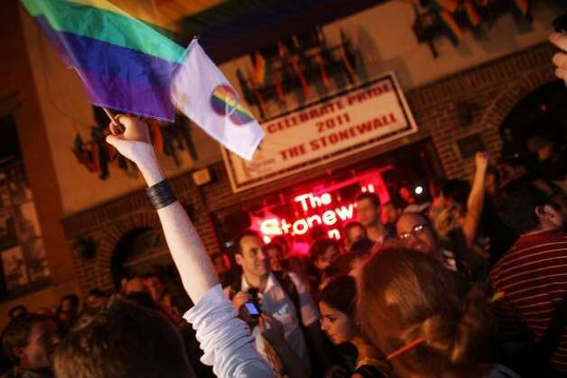 A reveler waves a gay pride flag in front of the historic gay bar The Stonewall after the passing of a bill legalizing gay marriage in New York. Photo: Spencer Platt, Getty