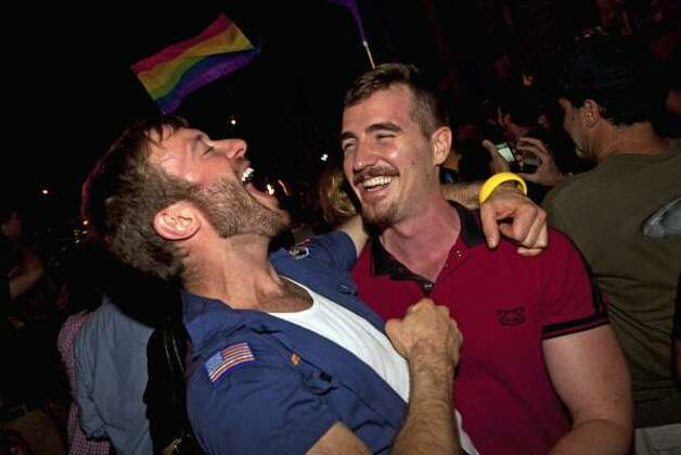 Colin Cunliffe, left, and Brewter Mccall, right, of Manhattan, celebrate the legalization of same-sex marriage in New York State outside the Stonewall Inn. Photo: John Minchillo, Associated Press