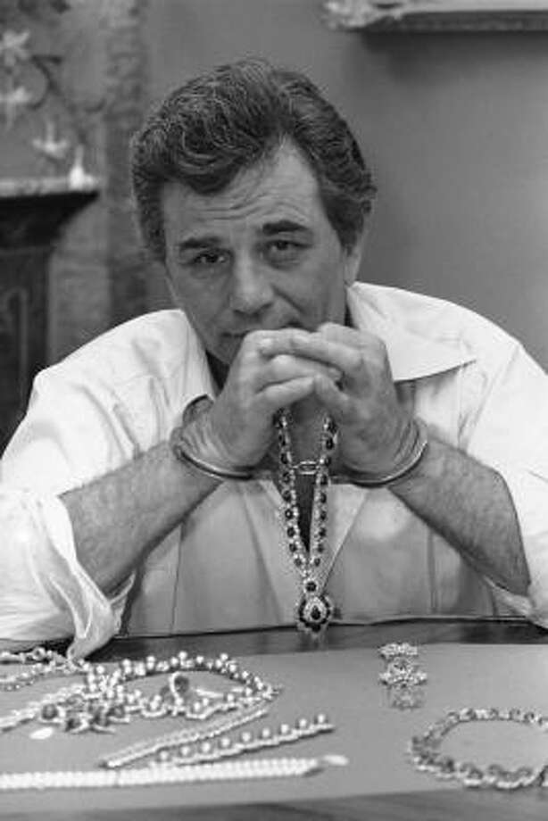 Actor Peter Falk poses with $8 million in diamonds, emeralds and gold while handcuffed during the filming of 1987 movie Happy New Year. Photo: Kathy Willens, Dapd