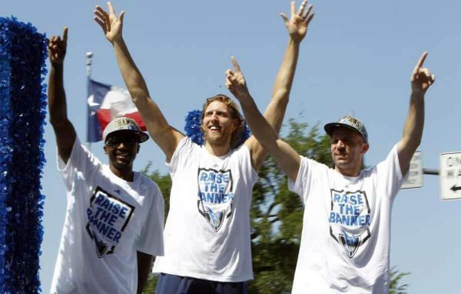 Dallas Mavericks players Jason Terry, Dirk Nowitzki and Jason Kidd wave to fans during the team's victory parade. Photo: LM Otero, Associated Press