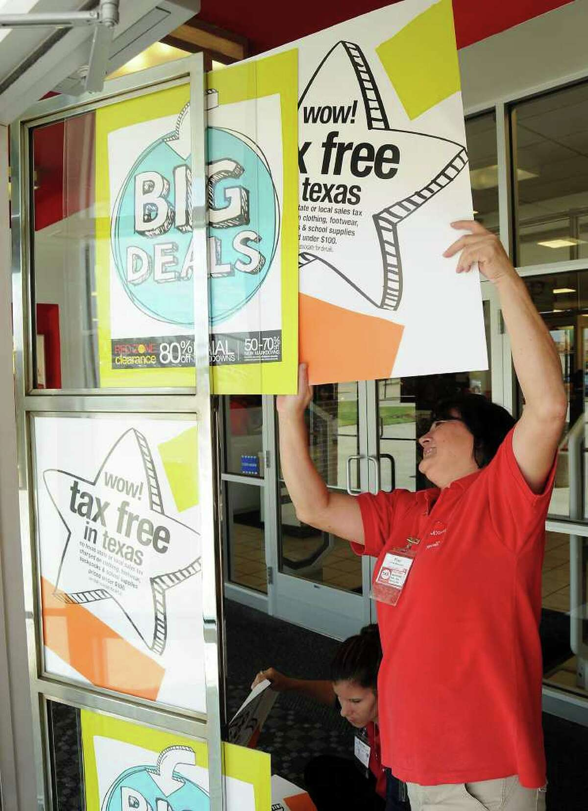 Employee Fran Atchison hangs a Tax-Free Weekend sign at the JC Penney store on Grand Circle Blvd. in Katy Wednesday Aug. 17,2011.(Dave Rossman/For the Chronicle)