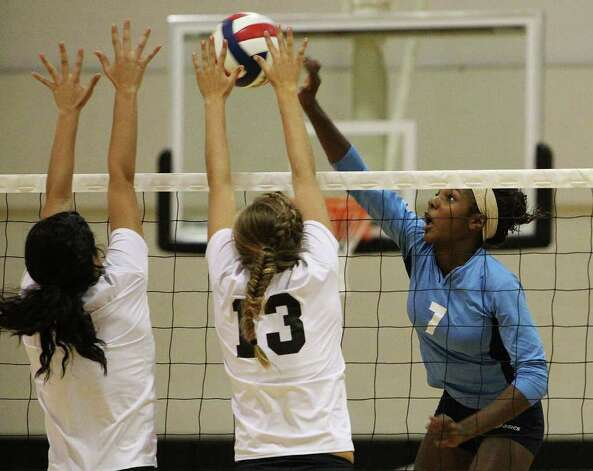 Johnson hitter Carnae Dillard (07) hits against Clark blockers Rosalyn Velasquez (left) and Megan Moe (13) in girls volleyball at Clark on Wednesday, August 17, 2011. Johnson defeated Clark in three straight games. Kin Man Hui/kmhui@express-news.net Photo: KIN MAN HUI, -- / San Antonio Express-News