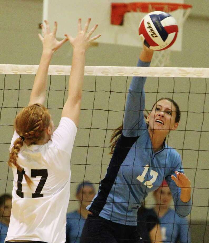 Johnson's Sarah Wilson (12) hits past Clark's Hunter Cole (17) in girls volleyball at Clark on Wednesday, August 17, 2011. Johnson defeated Clark in three straight games. Kin Man Hui/kmhui@express-news.net Photo: KIN MAN HUI, -- / San Antonio Express-News