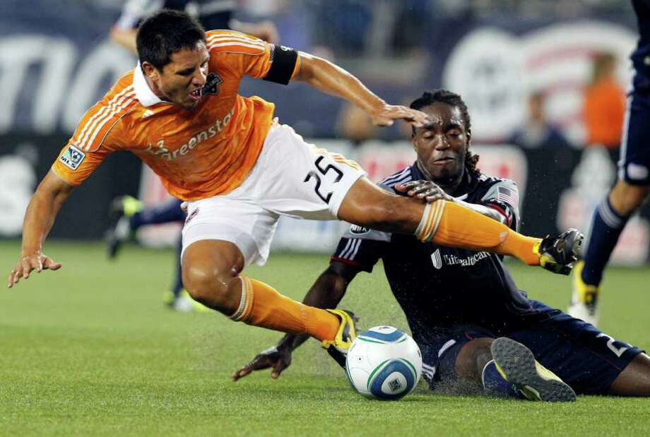 Houston Dynamo forward Brian Ching (25) is upended on a challenge by New England Revolution midfielder Shalrie Joseph, right, during the first half of an MLS soccer game in Foxborough, Mass., Wednesday, Aug. 17, 2011. (AP Photo/Elise Amendola) Photo: Elise Amendola, STF / AP