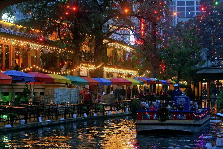 People riding a barge view the Christmas lights on the River Walk in 2007. A proposal before the City Council today would replace the traditional 85,000 incandescent lights with 1.76 million multicolored LED lights. Photo: Tom Reel/treel@express-news.net / SAN ANTONIO EXPRESS-NEWS