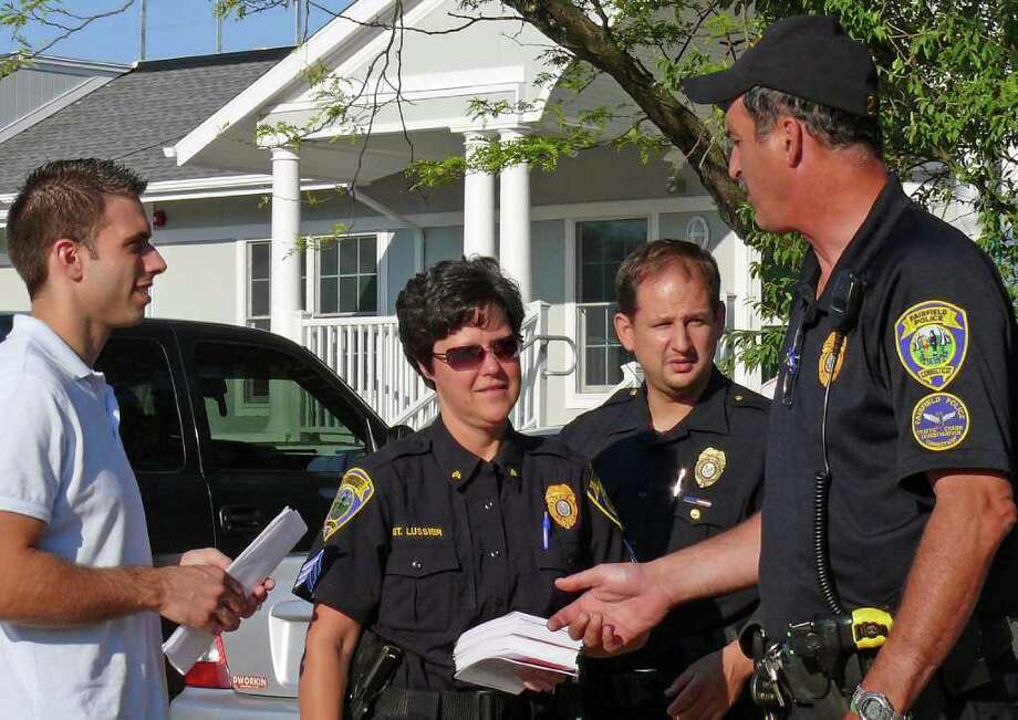 "Fairfield police officers get ready to fan out in the parking lot at Penfield Beach, looking for unlocked cars or valuables left in plain sight as part of their ""ticket tagging"" program to prevent car break-ins. Photo: Genevieve Reilly / Fairfield Citizen"