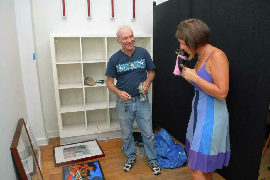 Tony Mobilia gets help from Norwalk 2.0 co-founder Maribeth Becker hanging his work at group show at the former Sweet Rexie's in Norwalk, Conn. on Friday August 5, 2011. Photo: Dru Nadler / Stamford Advocate Freelance