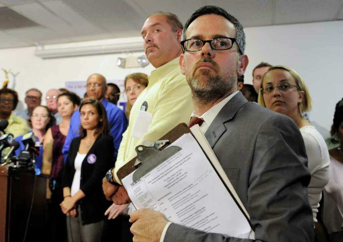 Matt O'Connor spokesman for The State Employees Bargaining Agent Coalition (SEBAC) right, listens to a question from the media as union members stand behind him during a news conference at a union office in Hartford, Conn., Thursday, Aug. 18, 2011. Connecticut's state employee unions announced Thursday that rank-and-file members ratified a labor savings and concessions agreement, giving Gov. Dannel P. Malloy the go-ahead to rescind thousands of layoff notices and forgo additional state budget cuts. (AP Photo/Jessica Hill)