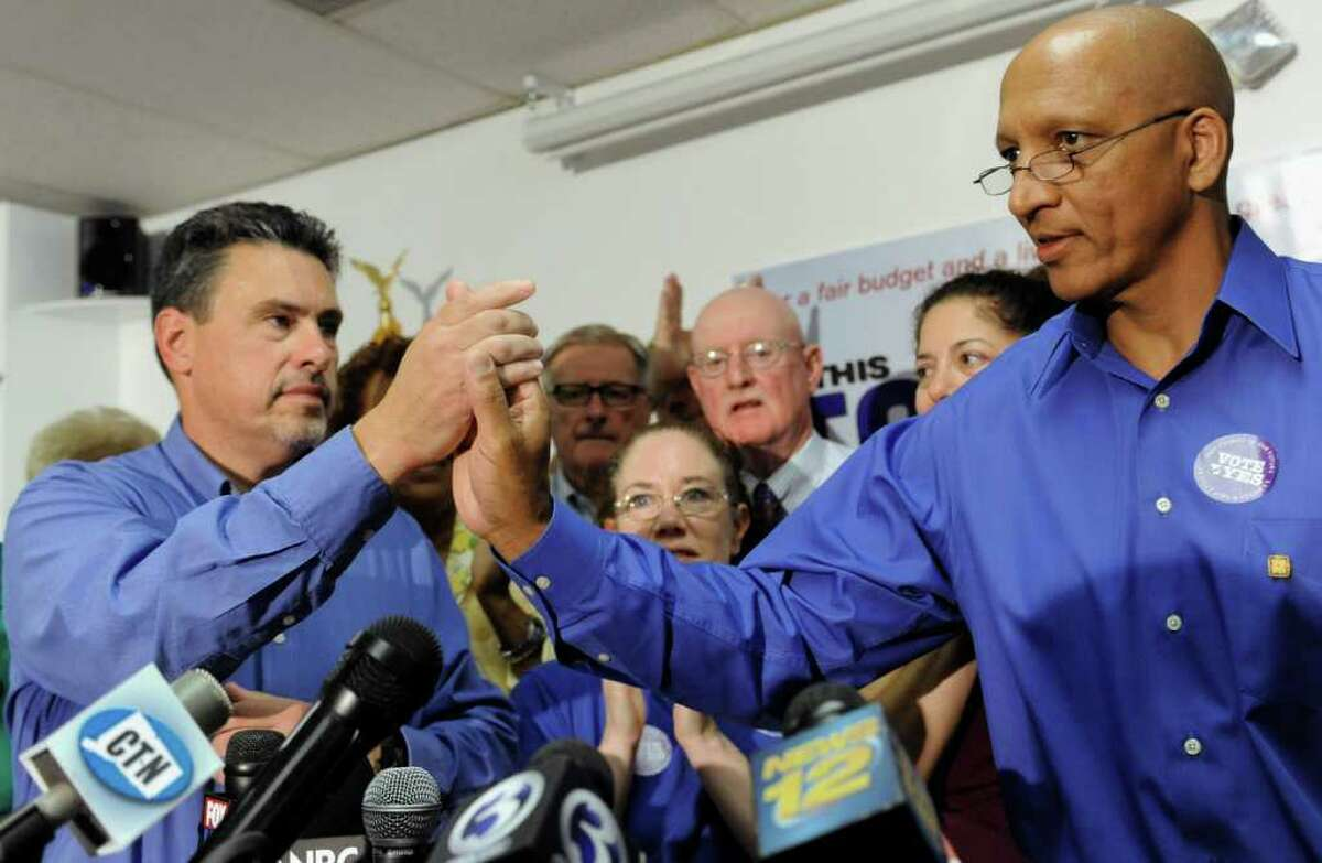 Ron McLellan, President of Connecticut Employees Union Independent (CEUI), left, celebrates with Robert Alves, District 1199 union member, right, as union members stand behind at a news conference in Hartford, Conn., Thursday, Aug. 18, 2011. Connecticut's state employee unions announced Thursday that rank-and-file members ratified a labor savings and concessions agreement, giving Gov. Dannel P. Malloy the go-ahead to rescind thousands of layoff notices and forgo additional state budget cuts. (AP Photo/Jessica Hill)