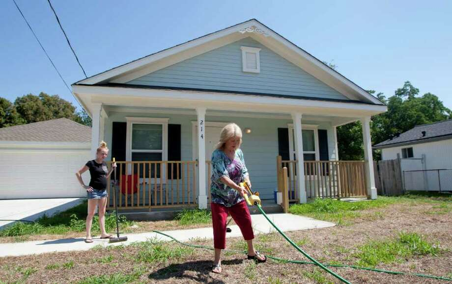 8/17/11: Baytown resident Barbara Bunn , and her grand daughter Heather Knight work in the front yard of  her new house at 214 E. Fayle St. , in Baytown, TX   Bunn lives in the 2 bedroom , 1 bath home with her husband, her grand daughter, niece, grand daughter and  great grandson. Bunn had her home severely damaged in Hurricane Ike, and only in the last few weeks moved into a new home built for her by Harris County (using federal funds). For the Chronicle: Thomas B. Shea Photo: For The Chronicle:  Thomas B. Sh, Thomas B. Shea