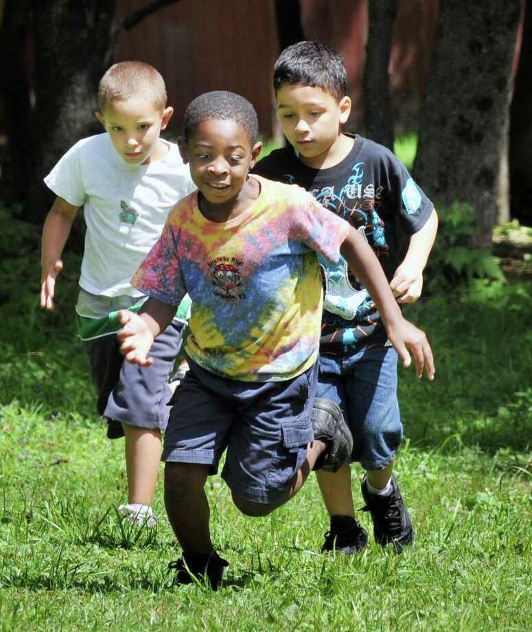 Summer campers, from left,  Joey Zych,6, Calvin Romero-Charles, 6, and Matthew Melendez,6, race to the mess hall for lunch at Camp Barker in Grafton Thursday Aug. 11, 2011. (John Carl D'Annibale / Times Union) Photo: John Carl D'Annibale / 00014166A