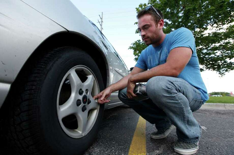 In this Aug. 11, 2011 photo, Jeff Swanson, 25, looks at the rear rotors on his 10-year-old Pontiac Grand Prix in Sterling Heights, Mich. Swanson, who was in the market for a new car just weeks ago, decided to keep his 10-year-old Pontiac Grand Prix for at least another year. Gyrations in stocks and talk of a weakening economy rattled Swanson's confidence about taking on another payment, even though his new job running a home for mentally disabled people seems to be secure. (AP Photo/Paul Sancya) Photo: Paul Sancya