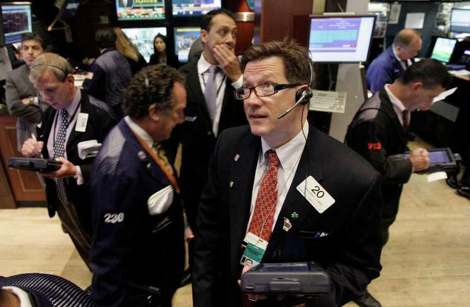Trader Christopher Forbes foreground right, watches prices as he works on the floor of the New York Stock Exchange Thursday, Aug. 18, 2011. (AP Photo/Richard Drew) Photo: Richard Drew